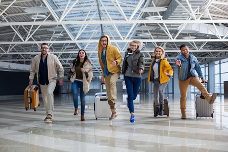 Foto für Full length portrait of group of tourist chasing each other at the airport. Their faces are joyous - Lizenzfreies Bild