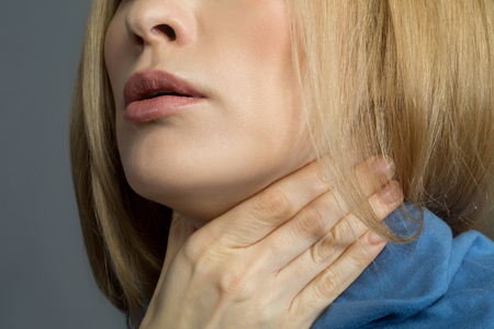 Foto de Sore throat. Close up of female chin, lady is holding her hand on neck covered with scarf. Isolated on background - Imagen libre de derechos