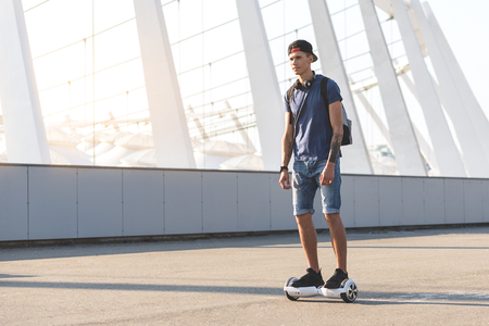 Photo pour Full length beaming man riding on hoverboard at street. Digital device concept. Copy space - image libre de droit