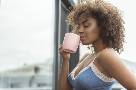 Photo for Happy young african lady expressing pleasure while tasting mug of delicious beverage outdoor. Copy space - Royalty Free Image