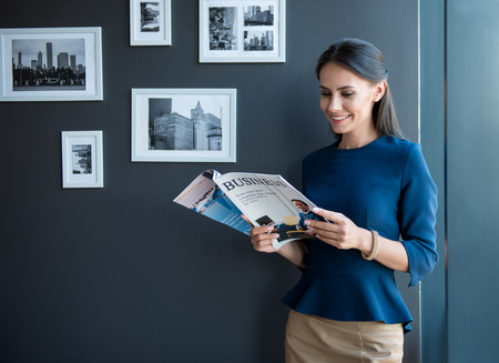 Photo pour Joyful working time. Optimistic stylish young woman is standing with business magazine and reading with pleasure. She is expressing joyfulness. Copy space in the left side - image libre de droit