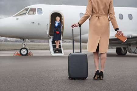 Photo pour Female going to airplane while holding baggage in hand. Happy air-hostess waiting for her. Occupation concept - image libre de droit