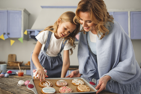 Photo for Satisfied mother and daughter standing in the kitchen and looking at cookies prepared for easter - Royalty Free Image
