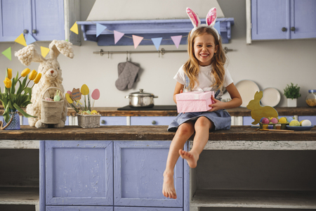 Photo for Portrait of glad little girl wearing rabbit ears on head resting in the cozy kitchen with present in hands. Copy space in left side - Royalty Free Image