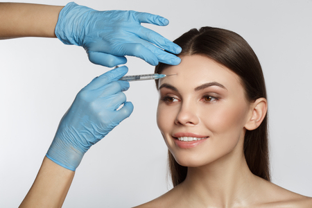 Photo pour Portrait of cheerful girl getting surgical facial correction. Beautician arm injecting liquid into her forehead. Isolated - image libre de droit