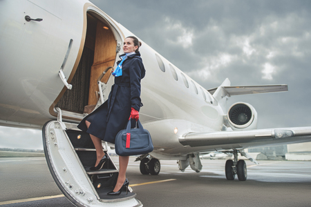 Foto de Full length portrait of cheerful young air-hostess entering airplane while holding baggage. Job concept - Imagen libre de derechos