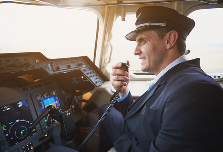 Photo pour Side view happy pilot talking by portable radio set in cabin of airplane. Conversation and occupation concept - image libre de droit