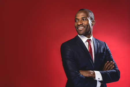 Foto de Full of joy. Waist-up portrait of cheerful cute young african businessman in suit is looking aside playfully while standing with crossed arms. Isolated background and copy space in the left side - Imagen libre de derechos