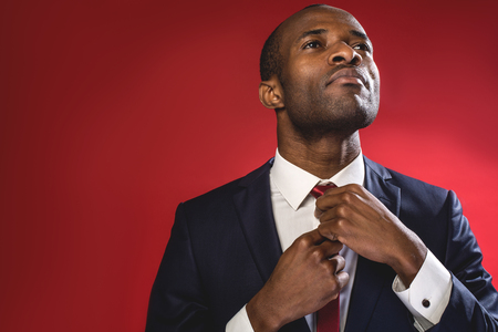 Foto de Serious business attitude. Elegant sucessful young man is standing and adjusting his tie. Copy space in the left side. Isolated on red background - Imagen libre de derechos