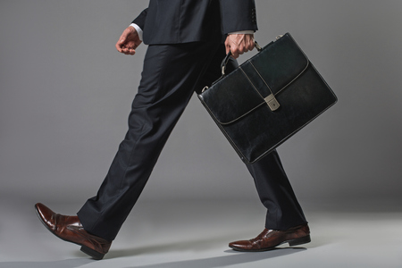 Photo for Low angle close up of male legs. Man walking in business suit with suitcase - Royalty Free Image