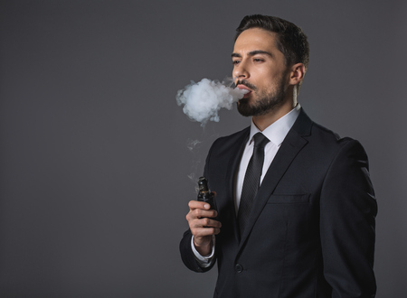Foto de Waist up portrait of thoughtful handsome man. He is standing and smoking. Isolated on gray background. Copy space in left hand - Imagen libre de derechos