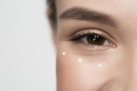 Foto de Facial cosmetics concept. Close up of smiley eye of girl. She is looking at camera with joy. Drops of moisturizer cream are around - Imagen libre de derechos