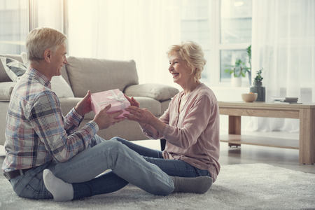 Photo for Retired couple with satisfied expressions relaxing on the floor indoors. Man giving present to woman - Royalty Free Image