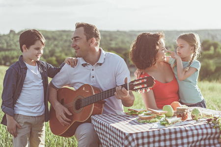 Photo pour Joyful father and son are singing favorite song to guitar. Woman is playing with daughter and smiling. They are sitting at table on summer meadow - image libre de droit