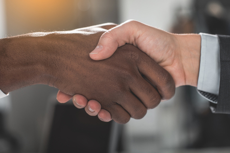 Foto de Good deal. Close up of firm strong handshake of business partners in office - Imagen libre de derechos