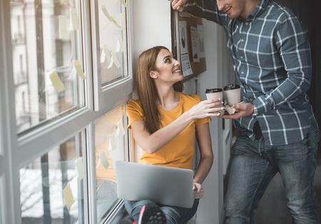 Photo for Enjoyed guy giving coffee to his partner at work. Woman accepting beverage with pleasure. Notebook is on her knees - Royalty Free Image
