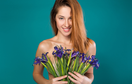 Photo pour Natural beauty. Portrait of charming naked young woman holding flowers which covering her breast. She is looking forward with seduction and smiling. Isolated - image libre de droit