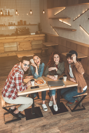 Foto de Top view of carefree guys and girls chatting in coffee shop. They are looking at camera and laughing - Imagen libre de derechos