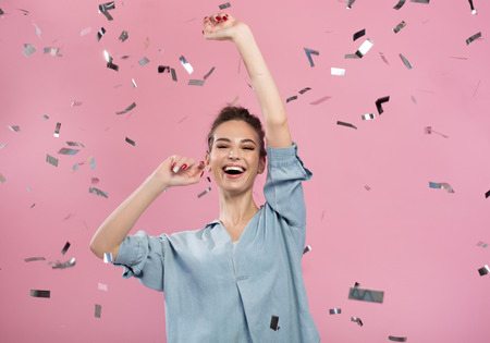 Foto de Best celebration. Cheerful optimistic girl is standing and exulting while raising her hands up with wide smile. Confetti are flying in air. Pink background - Imagen libre de derechos