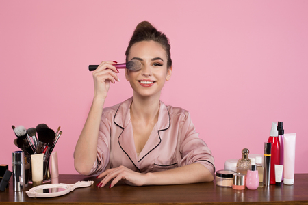 Photo for Portrait of optimistic young female cosmetologist is sitting at dressing table with cosmetics items and holding brush. She is looking at camera with smile. Isolated on pink background - Royalty Free Image