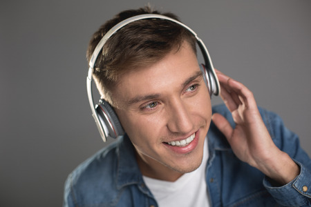 Photo pour Portrait of smiling man with headphones on head looking aside while enjoying melody. Isolated on background - image libre de droit