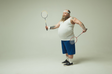 Photo pour Full length portrait of joyful fat man holding tennis rackets. He is standing and smiling. Copy space - image libre de droit