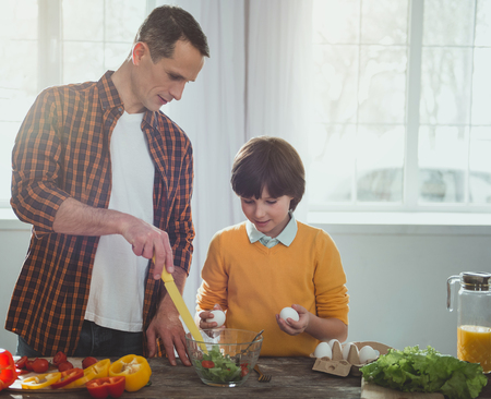 Foto de Parent and child standing at the kitchen table. Father pointing at bowl with greens, attentive kid holding eggs - Imagen libre de derechos