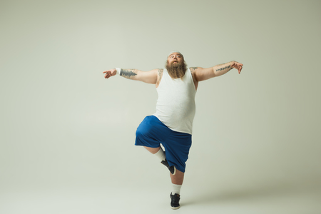 Photo pour Crane position. Full length portrait of calm thick guy standing on one leg while stretching arms sideways with grace - image libre de droit