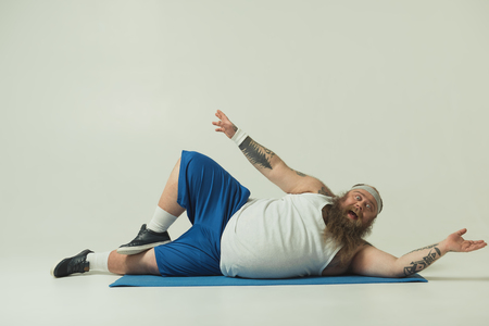 Foto de Portrait of crazy thick guy exercising on mat. He is looking at camera with excitement - Imagen libre de derechos