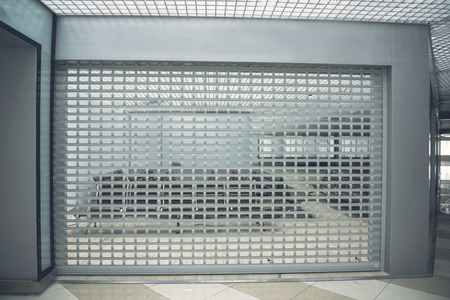 Photo pour Closed door to iron grid locating between two rooms. Modern chairs are opposite it - image libre de droit