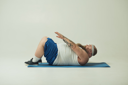 Photo for Sluggish fat man is doing sit-ups with effort. He is lying on mat - Royalty Free Image