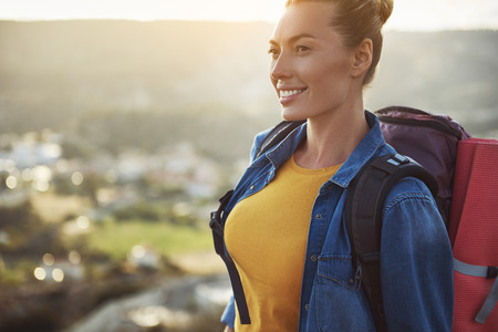 Foto de Portrait of female person with rucksack on her back looking aside and smiling. Focus on girl. Copy space in left side - Imagen libre de derechos