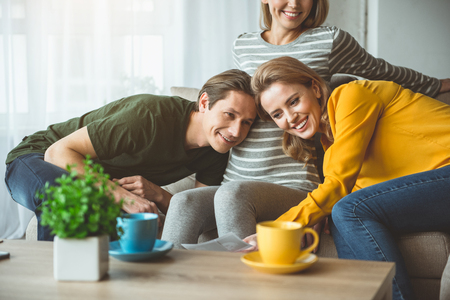 Foto de Portrait of glad married couple listening to female pregnant belly and smiling. They are looking at ultrasound picture with love. Surrogate motherhood concept - Imagen libre de derechos