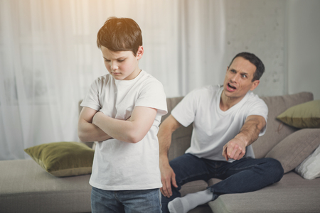 Photo for You are punished. Irritated father is yelling at his son. Abused child is standing with crossed arms in room - Royalty Free Image