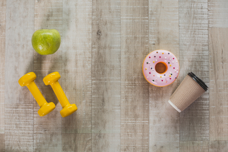 Photo for Sport and health versus harmful habits. Top view of green apple and yellow dumbbells lying opposite to coffee cup with donuts on wooden floor. Close up - Royalty Free Image