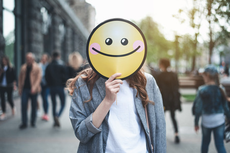 Foto de Be happy. Waist up portrait of trendy lady with round cheerful smile in her hand hiding her face. She is standing in the street and a lot of people on the background - Imagen libre de derechos