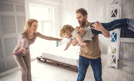 Foto de Doting father is holding son while little boy is showing arms like flying. Joyful mom is replicating kid behavior acting like plane. Loving parents and child are having fun in bright bedroom - Imagen libre de derechos