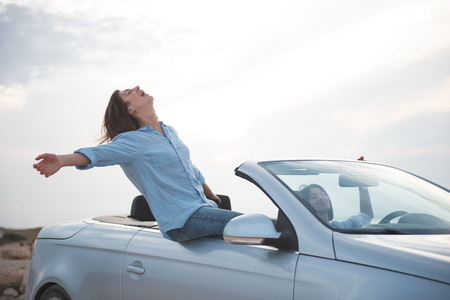 Photo for Full of admiration. Happy girl is sitting on fashionable cabriolet with her hands outstretched while expressing rapture. She is travelling by car along seashore with her friend female. Summer concept - Royalty Free Image