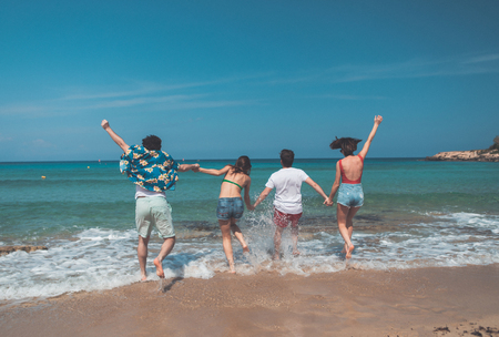 Photo pour Carefree young men and women are going into the water together. They are holding hands with joy while turning back. Having fun at the sea concept - image libre de droit