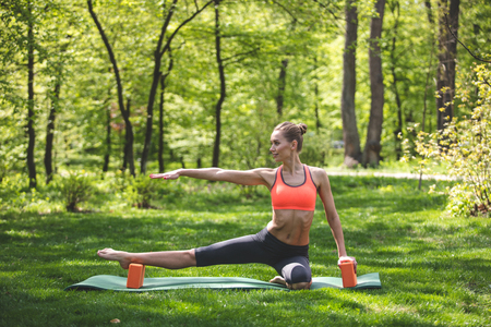 Photo for Grinning lady is exercising with blocks on mat on green lawn. She is stretching leg while bending another one. Training in countryside concept - Royalty Free Image