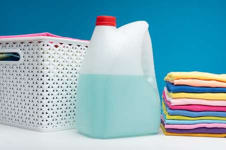Foto de Close up of container of bleach lying on white table at colorful t-shirts folded in pile. Wicker basket is aside - Imagen libre de derechos