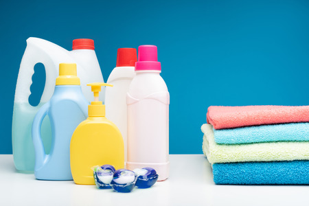Photo for Pick the one you like. Close up of selection of washing liquids put on white surface. Folded pile of towels is lying nearby - Royalty Free Image