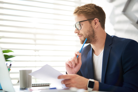 Photo pour Profile of handsome young male sitting at table and holding papers and blue pencil in hands. He is looking sideways absorbed in personal consideration of business ideas - image libre de droit