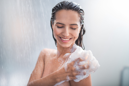 Foto de Portrait of happy girl taking shower with gel. She washing with puff - Imagen libre de derechos