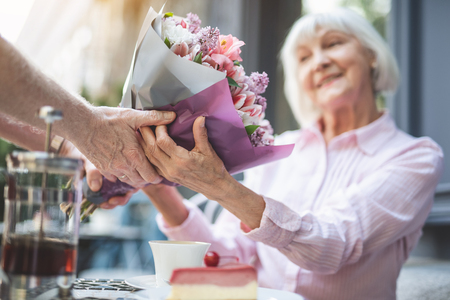 Photo for Focus on male hands holding bunch of flowers to smiling mature lady. She is taking present with pleasure and sincere gratitude - Royalty Free Image