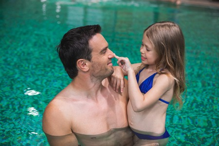 Foto de My daddy. Profile of happy father holding daughter in pool. Small girl is looking at man and touching his nose with smile. They are delighted to spend time side by side - Imagen libre de derechos