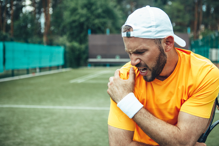 Photo pour Side view angry unshaven young man having pain in shoulder while keeping it with arm. He holding racket. Male having injury during game concept - image libre de droit