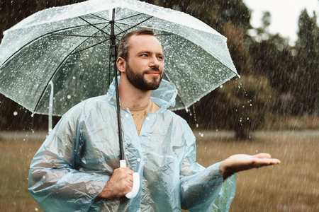 Photo for Waist up portrait of smiling male standing outside and holding umbrella. He is stretching hand in delight trying to catch water drops - Royalty Free Image