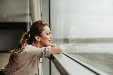 Photo for Side view happy woman dreaming while looking at window indoor. She having rest during labor - Royalty Free Image