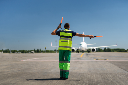 Foto de Time for landing. Aviation marshaller meeting passenger plane at the airport - Imagen libre de derechos